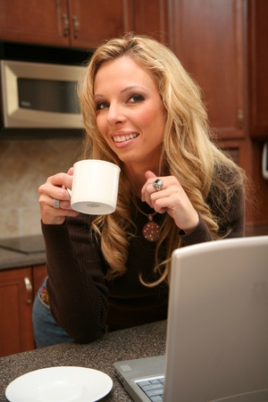 Woman drinking coffee standing in her luxury kitchen and working on her laptop photo