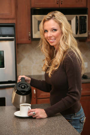 Woman drinking coffee standing in her luxury kitchen photo
