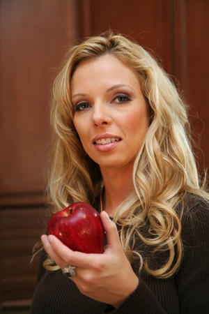 Woman about to eat an apple standing in her kitchen Banco de Imagens - 13408991