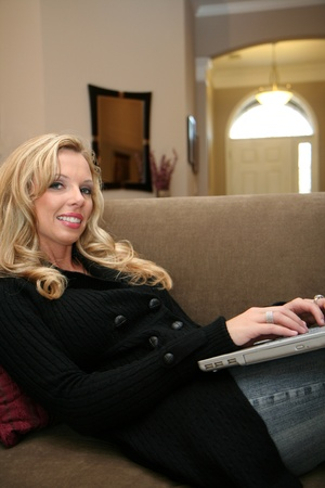 Young woman on her computer while laying on her couch photo