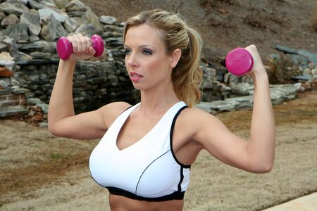 Woman lifting weights during a workout outside Stock Photo - 13409006