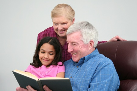 Grandfather and Grandmother reading a book to his granddaughter photo