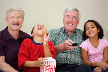 woman watching tv: Grandparents together with their family at home
