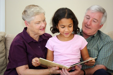 grandfather and grandmother: Senior Couple Sitting Together In Their Home With Granddaughter Stock Photo