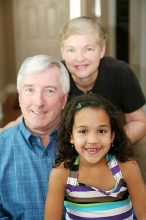 Senior couple together in their home with their granddaughter photo