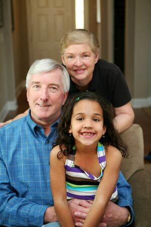 Senior couple together in their home with their granddaughter Stock Photo - 13409041