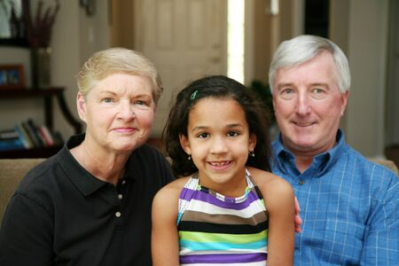 Senior couple together in their home with their granddaughter Stock Photo - 13409208