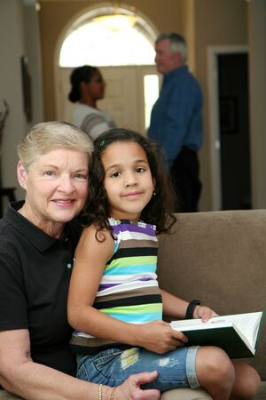 mexican girl: Grandmother holds her granddaughter while she reads a book Stock Photo