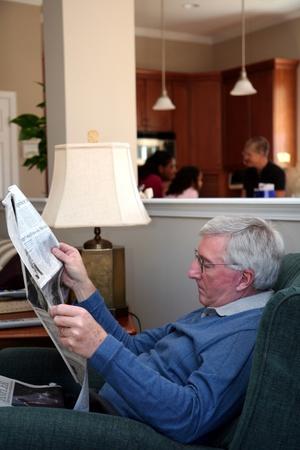 oude krant: De mens zit en leest de krant thuis met familie op de achtergrond Stockfoto