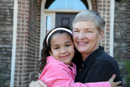 Happy Senior Woman with Grandaughter Outside In Front of House Stock Photo - 13408908