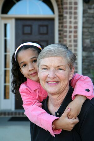 grandaughter: Happy Senior Woman with Grandaughter Outside In Front of House