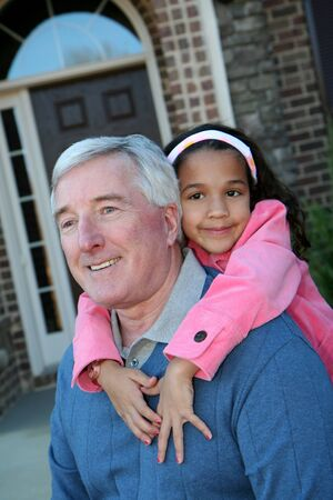 grandaughter: Happy Senior Man with Grandaughter Outside In Front of House Stock Photo
