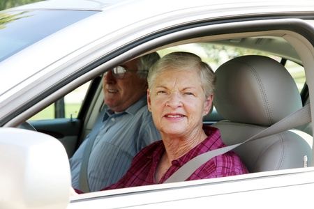 Senior citizen couple sitting in their car photo