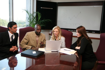 Boardroom meeting: Business Team sitting around a computer in an office Stock Photo