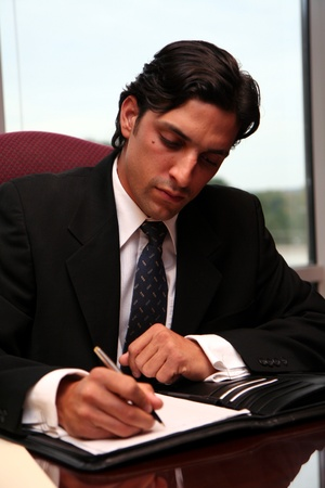 Businessman working in an office dressed in a suit Stock Photo - 13412587