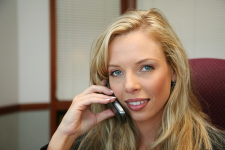 Young businesswoman on cell phone in an office photo