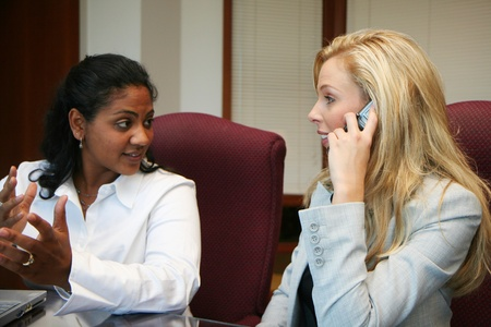 Young caucasian businesswoman with coworkers in an office setting photo