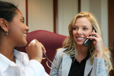 conference call: Young caucasian businesswoman with coworkers in an office setting