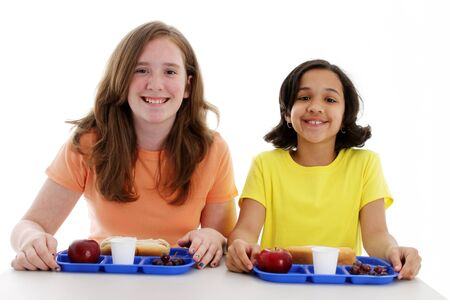 Kids eating their lunch together at school Stock Photo