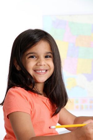 Elementary aged girl in her school classroom Stock Photo - 13399054