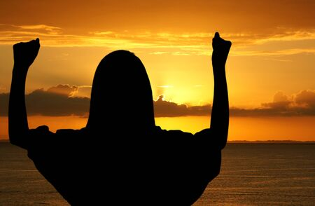 black worship: Girl with hands up while standing on the beach Stock Photo