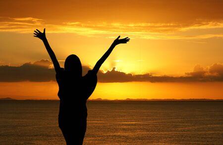 alabanza: Chica con las manos en alto mientras está de pie en la playa Foto de archivo