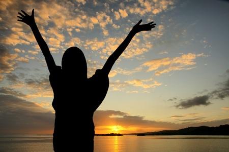 alabanza: Chica levantando sus manos durante la puesta de sol en la playa
