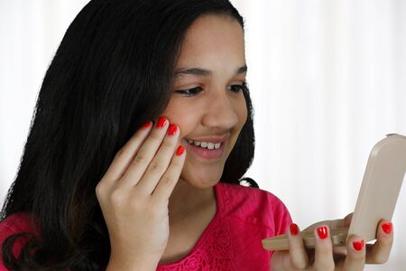 Teenage girl putting on makeup at her home photo