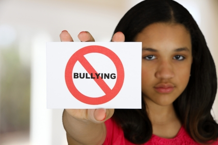 mean: Teen girl holding a card that says no bullying