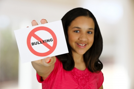 Teen girl holding a card that says no bullying photo