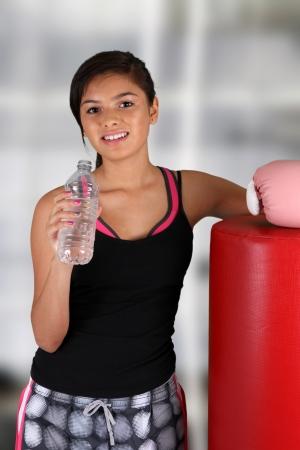 十代の少女は、ジムで水を飲む