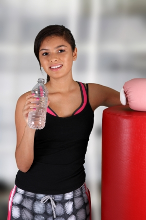 Teen girl drinking water at the gym photo
