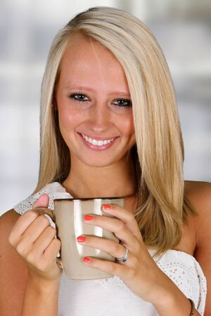 woman drinking tea: Young woman drinking coffee in her home Stock Photo