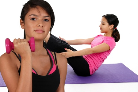 Girl Doing Yoga Pose in a Studio and another lifting weights photo