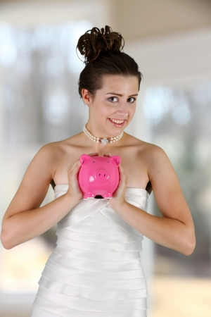 Woman in a wedding dress with piggy bank photo