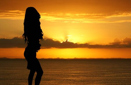 Woman standing on the beach watching the sunset photo