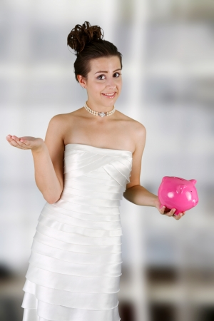 Woman in a wedding dress holding piggy bank photo