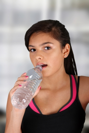 Teen girl drinking water at the gym Stock Photo - 14449805