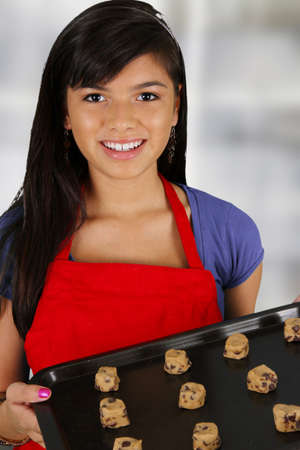 Teen girl baking cookies in her kitchen photo