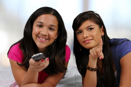 Teenage girl laying in her bed with her friend watching TV photo