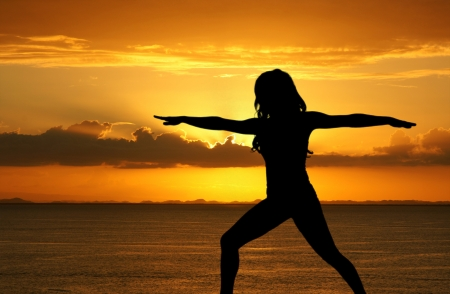 Woman doing yoga during sunset at the beach photo