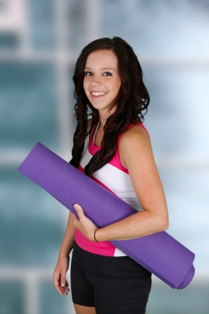 Teen girl standing with her yoga mat at the gym photo