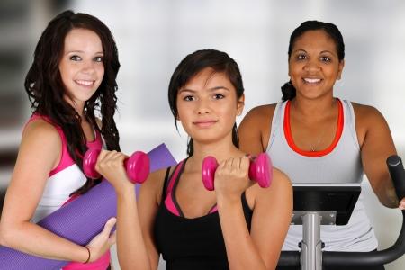 levantar pesas: Grupo de mujeres que trabajan en el gimnasio