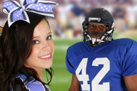 Teenage cheerleader with a football player on the field photo