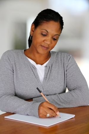 person writing: Woman working from home in her living room
