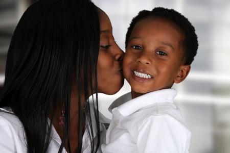 madre soltera: Mujer de pie en la sala de su casa con un niño