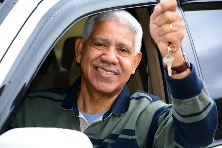 Senior man holding up keys to his new car photo