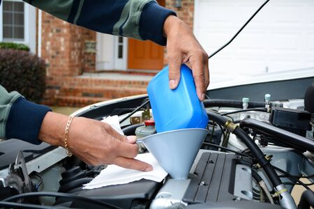 Mechanic werken aan een auto in zijn oprit