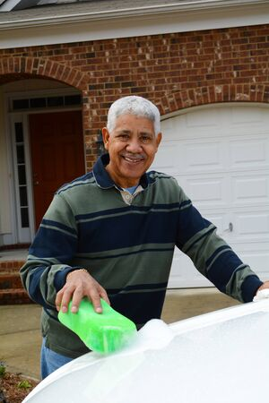 minority: Man washing his car in the driveway
