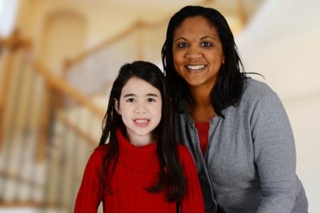madre soltera: La mujer y la hija de pie en el interior de su casa